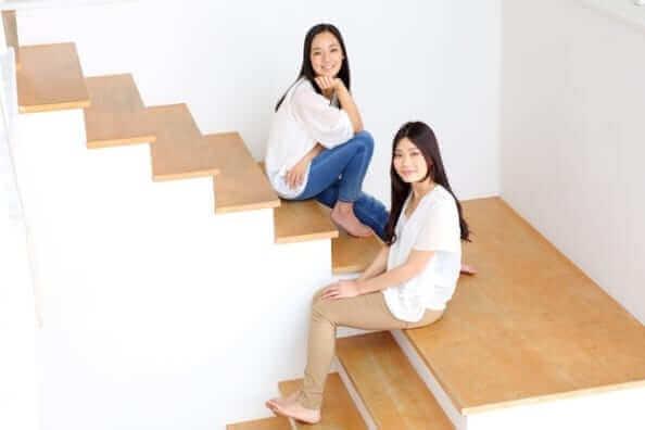 女性二人が階段に座っている