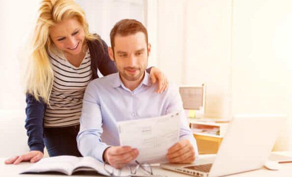 夫婦が書類を見て笑っている