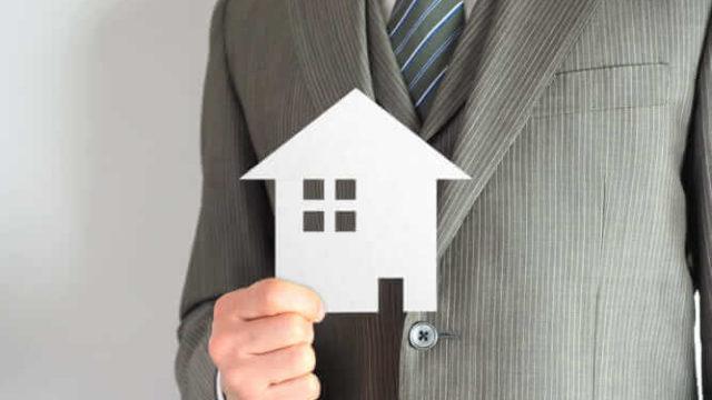 男性が家の模型を持っている
